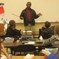 "Menhaden fisherman Ernest ""King"" Davis talking about his fishing days with children at Beaufort Middle School."