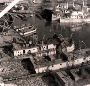 Aerial view of menhaden boats, looking loaded with fish to the scuppers, at one of the Beaufort fish factories, date unknown. You can see a net reel (for drying purse seines) on the upper left, and a trio of purse boats beneath the reel.
