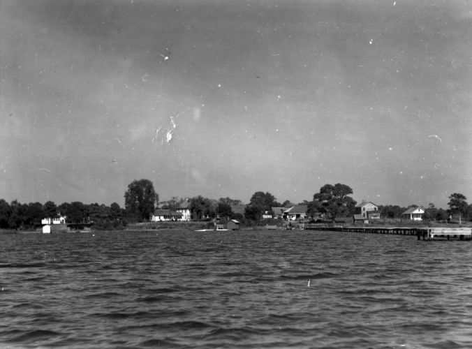 The village of Marines, ca. 1938-41, as seen from a boat on the New River. You can see Ollie Marine's general store immediately at the foot of the community wharf, partly obscured by a large oak. If you look close, you can also see the roof of his blacksmithing shed just to the left of the store. His gristmill is located on the far side of the store, so is not visible seen in this photograph. The store was located a dirt road that ended at the wharf.