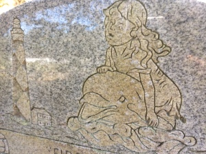 "A detail from the grave marker for Celia Faye Styron. Above her name, the marker reads, ""First Mate."" Next to her marker, a marker for Louis C. Styron, Jr. reads, ""Skipper"" and features a carving of the Cape Lookout Lighthouse and a sailing vessel."