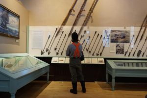 A visitor looks at the New Bedford Whaling Museum's collection of whaling harpoons. Courtesy, WBUR, public radio Boston.