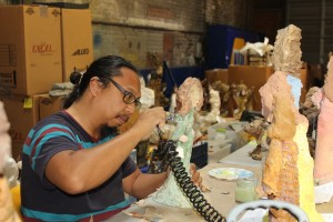 Conservationist Ben Caguioa working on one of Annie Hooper's Biblical figures in Wilson last summer. Photo by Lisa Boykin Batts, courtesy of The Wilson Times