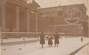 """Children walking by the old county courthouse in Tarboro on a snowy day, ca. 1890-1900. """"Ballard's Obelisk"""" was a popular brand of flour. """"D. Lichtenstein & Co. Grocers"""" was a local grocery started in 1874 by David Lichtenstein, the son of Prussian Jewish immigrants. After the Civil War, Tarboro had a sizable Jewish community. A local newspaper referred to a 2-block stretch of downtown as """"Little Jerusalem."""" Courtesy, Edgecombe County Memorial Library"""