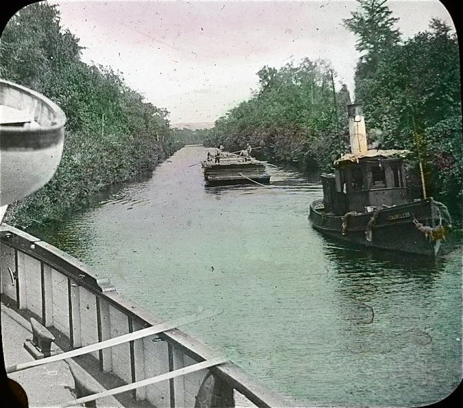 Tug Dauntless and lumber barge as seen from the bow of the lighthouse tender Violet, Albemarle & Chesapeake Canal, 1901. Image by Albert Ross, USN. Courtesy, Linda Garey