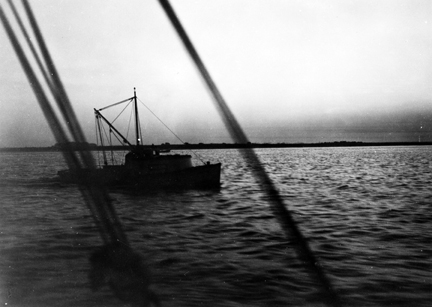 A shrimp trawler at dawn at the mouth of the Cape Fear River, 1938. Even after the Second World War, the classic Carolina shrimp boat was still a 25-foot wooden skiff, local-built, dragging a 15-foot flat-netted, cotton twine otter trawl and powered by a 3-8 horsepower automobile engine.Photo by Charles A. Farrell. Courtesy, State Archives of North Carolina