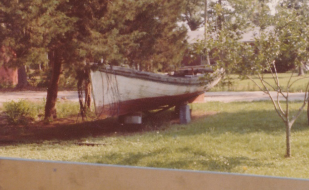 The Tom Dixon, a 28 and /12 ft. shad boat, in the backyard of Earl Willis, Jr.'s mother's house in 1980. George Washington Creef built her ca. 1891.  Mack Gaskill had given the boat to Earl in the 1970s. After H. R. Creef restored her, Earl donated the boat to the N.C. Maritime Museum in Beaufort, N.C. Photo by Mike Alford