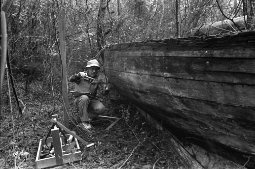 Mike Alford recording the construction details and midship section shape of a shad boat found in the woods on the north side of Roanoke Island probably in the 1980s. Courtesy, Mike Alford