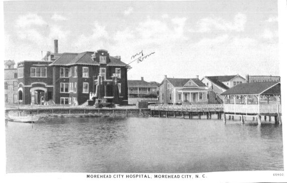 "Postcard from Russell Coles of the Morehead City Hospital with ""my room"" marked in his hand. Whether Coles was in the hospital for a fishing injury or for his rheumatism or another ailment is not clear. He was evidently a patient sometime between 1918 and 1925. Though Dr. Benjmin Franklin Royal established the hospital in 1911, the original building only had 7 beds. The building on the postcard opened in 1918. Courtesy, Walter Coles, Sr., Coles Hill, Va."
