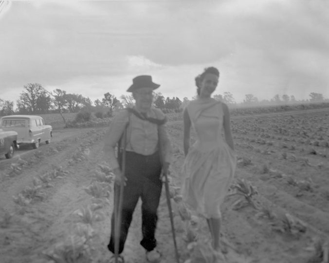 Tobacco Queen Shirley Bagwell visits W. H. Dail's farm to highlight an outbreak a plant disease called black shank on tobacco crops, 1957. Courtesy, Joyner Library, ECU
