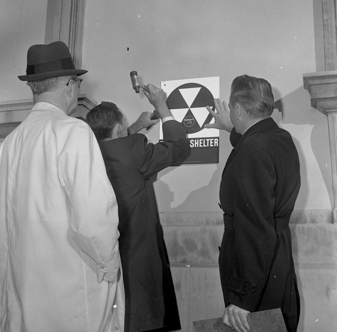 Men posting a nuclear fallout shelter sign on one of Greenville's public buildings. Courtesy, Joyner Library, ECU