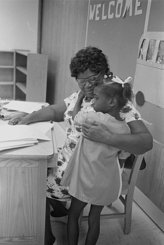 A teacher comforting a child on her first day of school, August 1967. Courtesy, Joyner Library, ECU