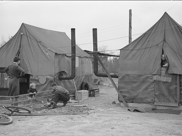 Family at a migrant camp of Ft. Bragg construction workers at a tent camp near Fayetteville, 1941. They rented tent space for $1.00 a week. Photo by Jack Delaney. Courtesy, Library of Congress