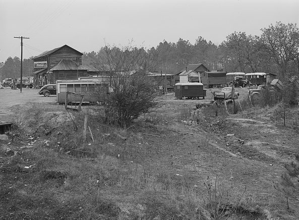 A migrant camp of Ft. Bragg construction workers next to a general store in Manchester, N.C, 12 miles from Fayetteville, Mar. 1941. The workers and sometimes their families lived largely in little trailers, trucks, tiny bunkhouses & even an old trolley car. Photo by Jack Delano. Courtesy, Library of Congress