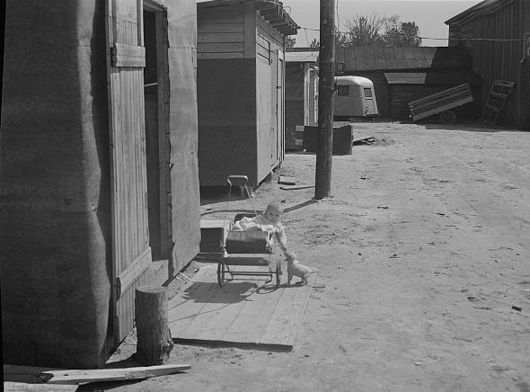 A baby in its stroller in a settlement of shacks built to house Fort Bragg construction workers, near Manchester, 1941. Photo by Jack Delano. Courtesy, Library of Congress