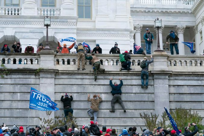 Supporters of Pres. Trump climb the wall on the West Wing of the U.S. Capitol after overrunning police barricades. Photo by Jose Luis Magana, AP.
