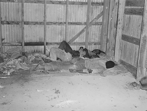 Belcross, N.C., 1940. Sleeping accommodations were spartan: potato sacks for beds, a warehouse for a bedroom. Photo by Jack Delano. Courtesy, Library of Congress