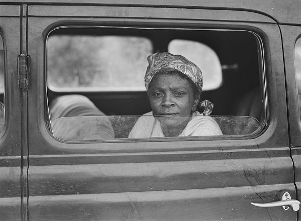A migrant laborer waiting to begin her journey from Camden County, N.C. to other fields in Cranberry, N.J. 1940. Photo by Jack Delano. Courtesy, Library of Congress