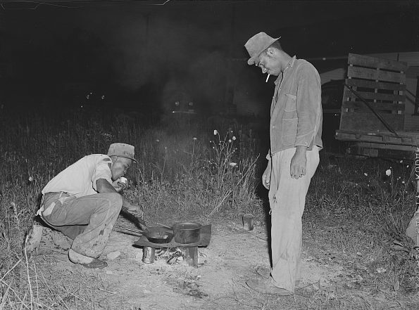 Belcross, N.C., 1940. Migrant laborers at a potato grading station cook their supper of potatoes and salt pork. Photo by Jack Delano. Courtesy, Library of Congress