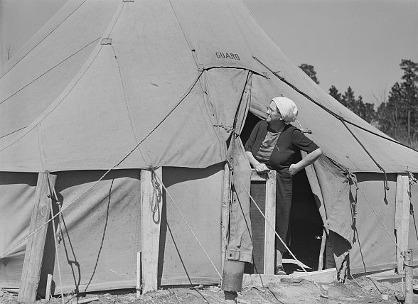 Near Fayetteville, N.C. A woman peering out a tent in a migrant camp, 1941. Photo by Jack Delano. Courtesy, Library of Congress