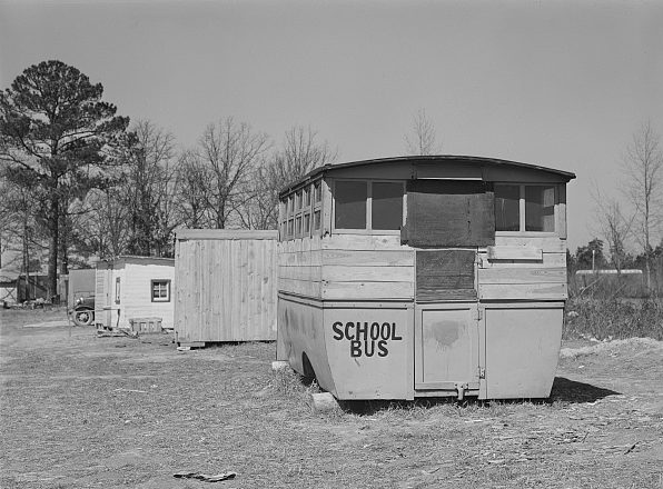 Another migrant camp near Fayetteville, N.C, 1941. The nearest shack was an abandoned school bus. Photo by Jack Delano. Courtesy, Library of Congress