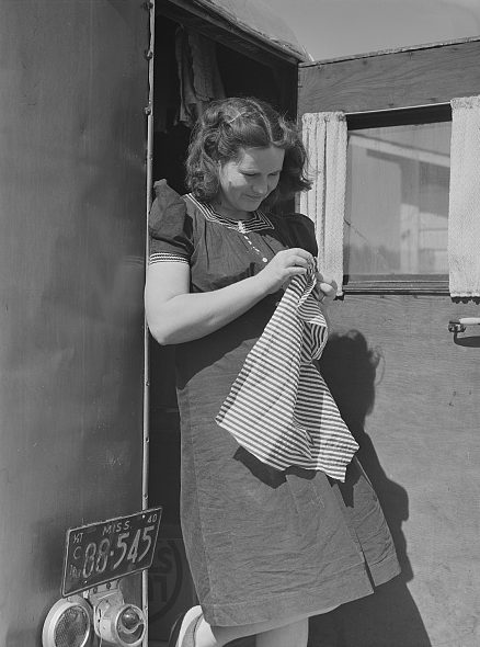 "Near Fayetteville, N.C., 1941. The photographer, Jack Delano, described this woman as a ""former circus performer."" She was traveling with her husband, a construction worker at Ft. Bragg. Their trailer's license plate is from Mississippi. Courtesy, Library of Congress"