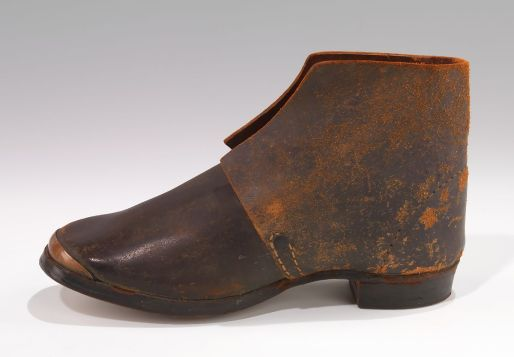"""Brogans may have been going out of fashion in Elizabeth City, but practically every rural working man and many a woman in eastern N.C. still wore them. They were heavy, ankle-high work boots, made of coarse, untreated leather and with a nailed or pegged sole. They were the archetypical footwear of soldiers, slaves and working people and their use dated back to the British Isles as early as the 16th century. The name """"brogan"""" apparently derives from an Old Irish or Scotch word for shoe. This brogan is actually in the collection of the Metropolitan Museum of Art in New York City."""