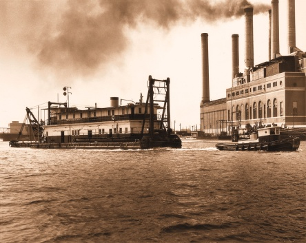 Undated photograph of a tug hauling a dredge in Norfolk Harbor. Many of the dredges that worked on the Intracoastal Waterway in N.C. were based in Norfolk. Many of the workers lived on the vessel for years at a time. Courtesy, Norfolk Dredging Co.