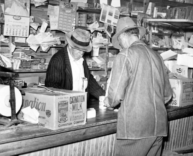 """This is either Johnny Henry Fulcher (Jim's brother) at his store in Fulcher's Landing or Jim Fulcher behind the counter at his brother's store. The store was on the bottom floor of a big house next to Jim Fulcher's fish house. Many years later John Henry's daughter Edna Fisher recalled her father: """"I have heard my mother tell how Papa would get up and go out 'in the midnight' to fish. He would return home early in the morning, in time to prepare breakfast for the children. (He was a widower with 5 children.).... After he grew older and no longer able to fish, he opened a store at the Landing."""" All 5 of the children eventually built homes within sight of it. """"Every evening we would all get together at 'Papa's store' and just sit around the little stove and share the happenings of the day."""" John Henry lived in the back of the building. Edna Fisher recalled her father's last days especially well. """"Every day after Papa ate his lunch, which usually consisted of fried fish and homemade biscuits, prepared by one of his daughters, he would lie down in the sunshine on the side porch of the house. One of the grandchildren would come and gently rub his head until he went to sleep."""" Photo by Charles A. Farrell. Courtesy, State Archives of North Carolina. Excerpt from The Heritage of Onslow County, N.C. (Jacksonville, N.C.: Onslow Co. Historical Society, 1983)"""