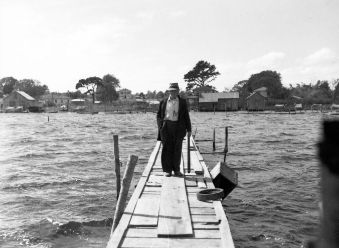 """Jim Fulcher on his dock. His father, Joseph Fulcher, first came to the New River from a fishing village known as Davis Shore, 60 miles to the east in the """"Down East"""" part of Carteret County. That was sometime between 1870 and 1880. At first, according to family lore, he and another Davis Shorer, Kenneth Davis, put up a tent and fished out of their campsite. Jim Fulcher's granddaughter, Rosetta Ward, told me that she always heard that Joseph eventually went back to Davis Shore and told his family that, on the New River, """"Fish were so plentiful that they were jumping in the boat and the fritters were growing in the fritter trees!"""" (I assume he was talking about oyster and clam fritters!) According to Ms. Ward, other Fulchers from Davis Shore and another, nearby village, Stacy, eventually followed Joseph back to what became known as """"Fulcher's Landing."""" Photo by Charles A. Farrell. Courtesy, State Archives of North Carolina"""
