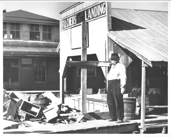 """Jim Fulcher at his fish house. His granddaughter, Rosetta Ward, remembered him when she was a very little girl. She said they called him """"Old Man Fulcher"""" or """"the patriarch of Fulcher's Landing."""" She recalled how he settled his accounts with the local fishermen on Friday nights and had a """"camp house"""" behind the store, where duck hunters would stay. Her mother and her sisters would clean the ducks and cook them, while the boys did chores like bringing wood for the stove. He lived in a big house on a hill, had 5 children and had the only telephone in the village. She told me that she remembered the feeling of his mustache when she used to hug and kiss him. Photo by Charles A. Farrell. Courtesy, State Archives of North Carolina"""